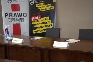Stół prezydialny wraz zdwoma krzesłami.
